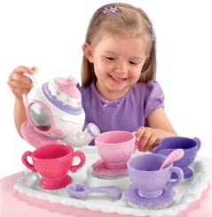 Kid serving tea to everyone from her little tea set