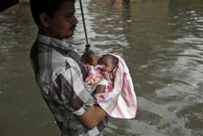 "A father carries his newly-born baby as he takes his baby home from a maternity hospital, through a flooded street during ""World Population Day"" in Kolkata"